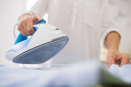 Iron, ironing. Female thin hands holding modern iron with quality sole over white cloth, positive