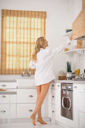 Morning mood. Long-haired adult woman in snow-white shirt barefoot on tiptoe in morning in light kitchen