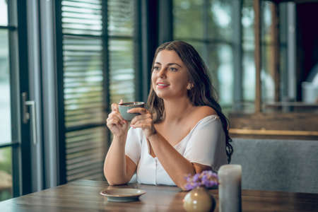 Harmony, mood. Pretty young pensive woman drinking coffee in good mood in afternoon in cafe