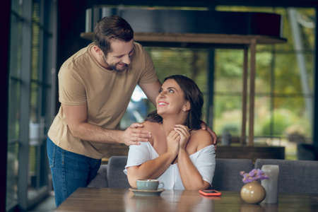 Meeting, hug. Smiling caring man hugging shoulders of joyful woman with long hair sitting at table in cafe
