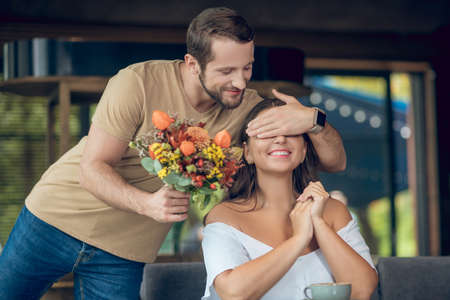 Lucky surprise. Joyful young bearded man with bouquet covering eyes of smiling woman sitting in cafe