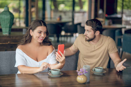 Pastime, cafe. Satisfied smiling woman showing smartphone and resentful serious gesturing man sitting with coffee in summer cafe