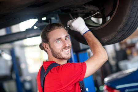 Maintenance. Happy young bearded man doing auto repair with his hand near car wheel of raised up car