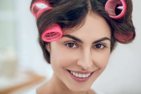 Close-up face of beautiful young woman in hair curlers
