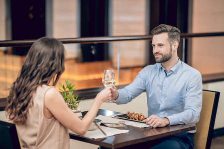 A couple having a dinner at the resaurant and saying a toast
