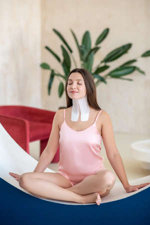 Cute woman in pink lingerie and tapes on her neck looking peaceful