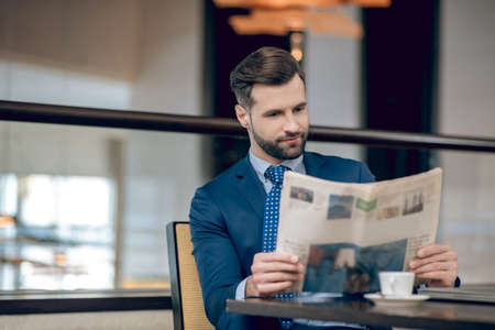 Elegant businessman in a nice suit reading a morning newspaper