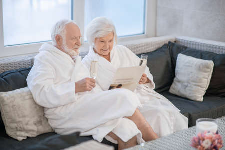 Senior couple in white robes having great times in spa salon and looking relaxed