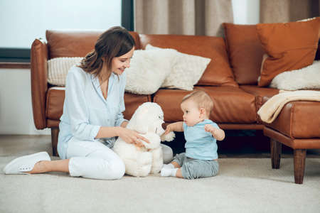 Mom showing teddy bear to interested child Stockfoto