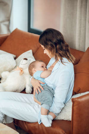 Mom feeding her baby sitting on couch