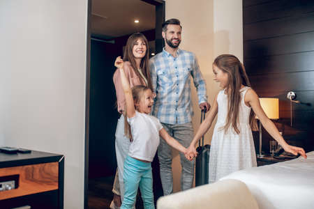 Young sweet family standing in the room and looking excited Stockfoto