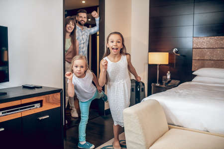 Two girls having fun in the room, parents watching them