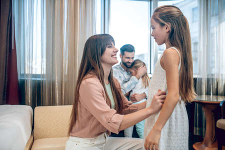 Mom dressing her daughter and looking happy