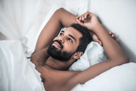 Waking man looking pensively lying in bed