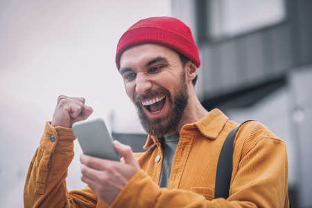 Young bearded man in a red hat looking at his phone and feeling happy Reklamní fotografie