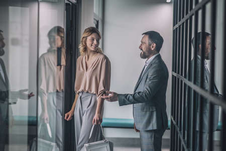 Business friendly man inviting his female colleague to office