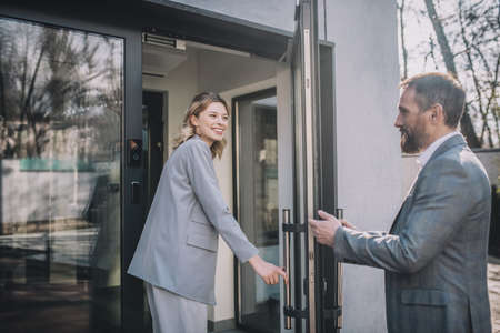 Woman entering office and man opening door Banque d'images