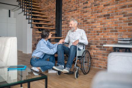 Dark-haired young woman sittingnear her handicapped husband Reklamní fotografie