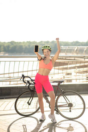 A girl with a bike standing at the bridge with a smartphone in hands