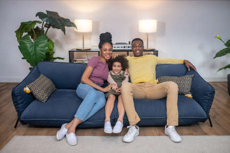 Darkskinned little girl and parents sitting on sofa