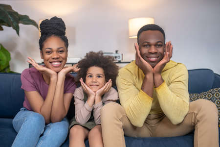Man woman and little girl cheerful sitting on couch Stockfoto