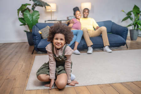 Daughter on floor and hugged parents on couch Stockfoto