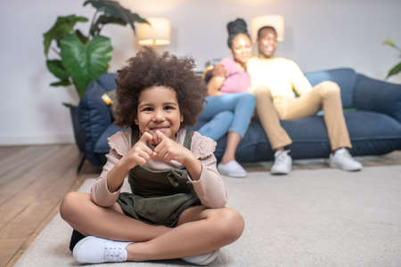 Girl showing heart with fingers and parents behind Stockfoto