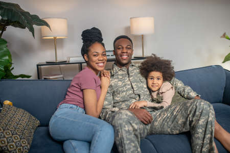Little girl woman and military man sitting on couch