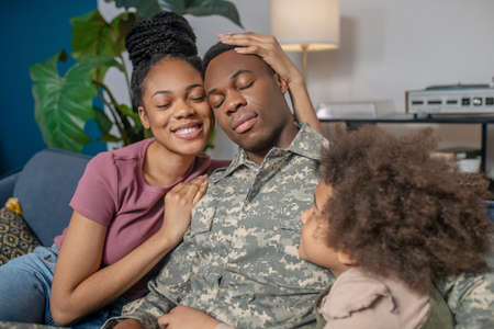 Woman hugging military husband and little girl Stockfoto