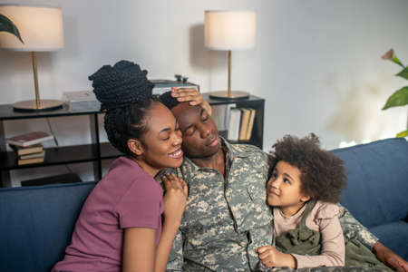 Military man with wife and little daughter at home