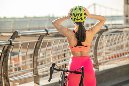 Young cyclist in bright sportswear standing at the bridge Imagens