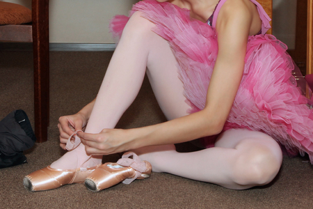 Ballerina sitting on the floor tying Pointe shoes Stock Photo