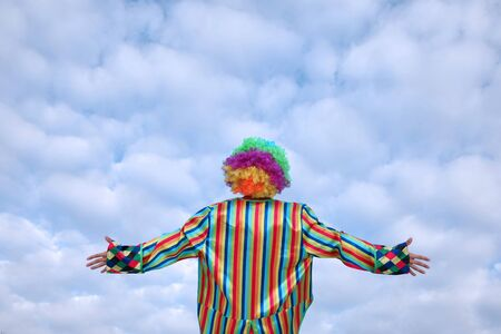 Clown stands with his back to us against the sky with beautiful clouds