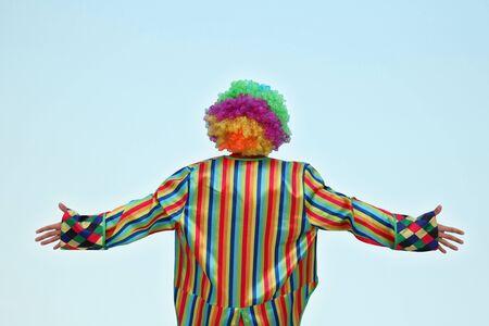 Clown debout, nous tournant le dos, isolé sur un fond bleu clair