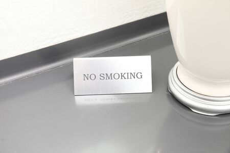 Silver sign that says No Smoking on the table