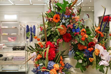 Exotic flower arrangement in a womens clothing store. From orange gerberas, yellow, red and blue of various colors Stockfoto