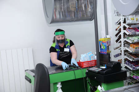 Seller-cashier in a medical mask, protective screen and gloves handles the counter and cash register of the store