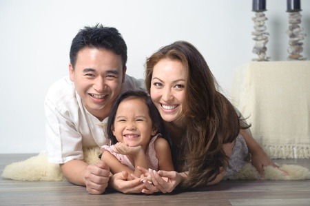 family living: Happy Asian Family in the Living Room Stock Photo