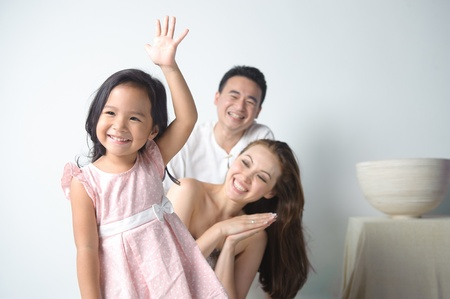 happy asian family: Child raising her hand in front of her happy family