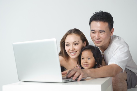 Asian family using the laptop with the daughter photo