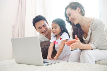 laptop asian: Familia Feliz asi�tico que usa ordenador port�til con hija Foto de archivo