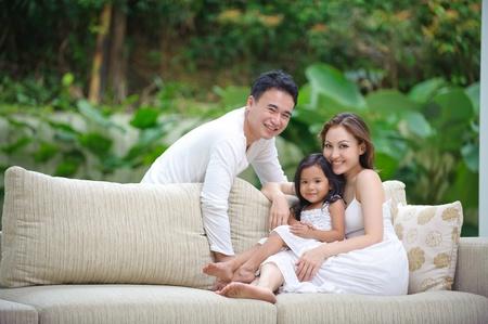 divano: Famiglia Asian godendo del tempo insieme in salotto Archivio Fotografico