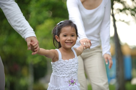 eurasian: Little girl smiling in the park while with parents