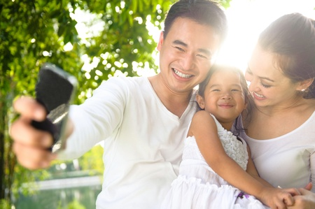 Asian Family Taking Photographs in the park Stock Photo - 11187605