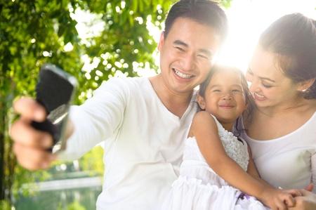 family in park: Asian Family Taking Photographs in the park