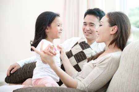 familia feliz: Familia asi�tica feliz que juega con la hija en la sala de estar