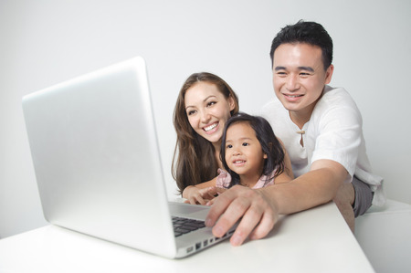 Asian family using the laptop with the daughter