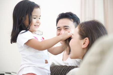 gl�ckliche menschen: Gl�ckliche asiatische Familie spielt mit Tochter im Wohnzimmer Lizenzfreie Bilder