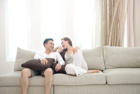 Glückliche asiatische Paar sitzt auf dem Sofa genießen jede andere Firma