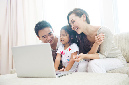 Happy Asian Family using laptop with daugther photo